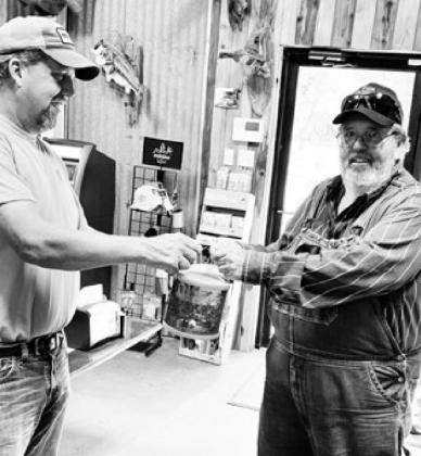 Kenny Kavanaugh (left) of K&M Coffee, Corks & Camo, hands a bucket of crickets to a customer. Suppliers have experienced a shortage of crickets recently due to an increase in fishing during the pandemic. Submitted photo