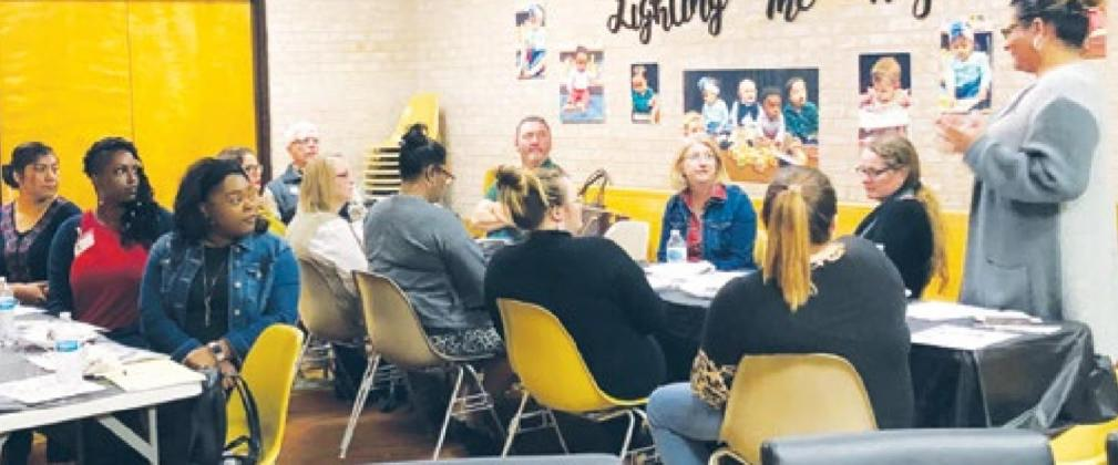 Mary Barrios (far right standing) speaks to a group of community members gathered for a recent Community Outreach meeting at the Union Parish Library. Gazette photo by BYRON AVERY