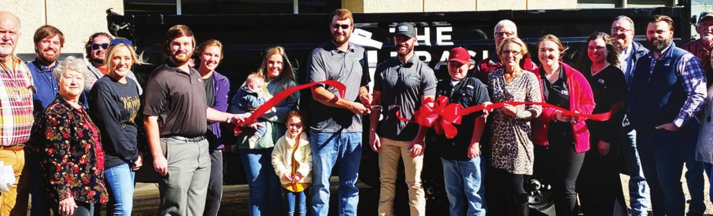 The ribbon cutting for The Trash Guys officially kicked off their Union Parish business. Jordan Powell (center, left) and Dylan Scott (center, right in cap) cut the ribbon in a Union Parish Chamber of Commerce celebration. Gazette photo by Byron Avery