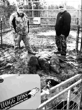 Submitted photo UPSO deputy Peyton McKinnie (right) shows some hogs he trapped on his property. Feral hogs are a menace to landowners, causing millions of dollars in damages.
