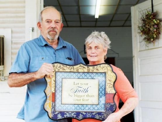 Brian and Susie Halley, founders of the Trees of Righteousness ministry, display a sign they came across while going through stacks of donated items. Gazette photo by DONNA BUNCH